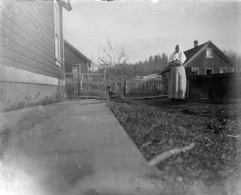 Woman in front of house.
