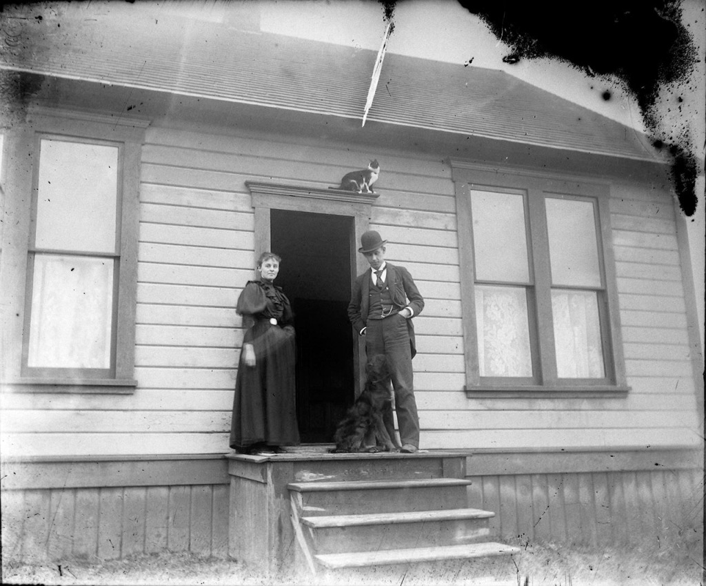 A couple with their dog and cat at the door.