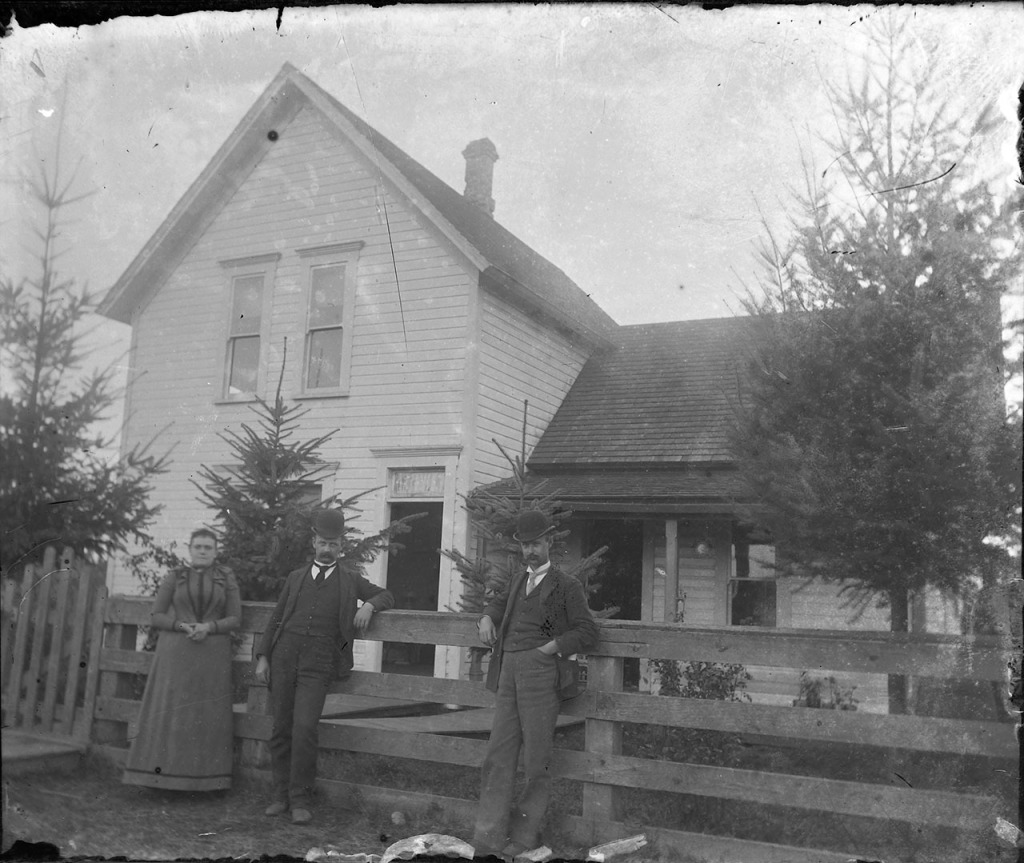 Two men and a woman lean on a fence near their house.