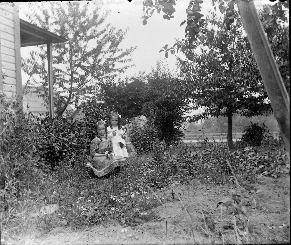 Two girls play witha doll in their yard.